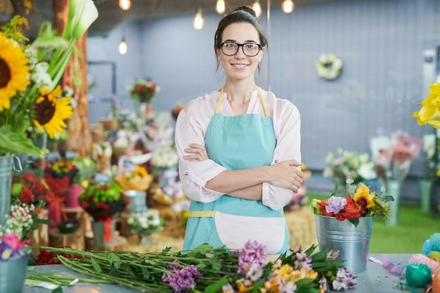 Женщина позирует в цветочный магазин