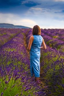 Женщина позирует в цветочных полях лаванды