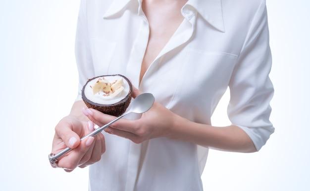 Женщина позирует в студии с натуральными кокосами, в которых подается десерт. органическая еда. смешанная техника