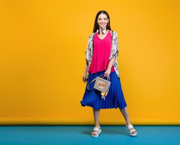 세련 된 여름 패션과 가방 화려한 분위기에서 포즈를 취하는 여자