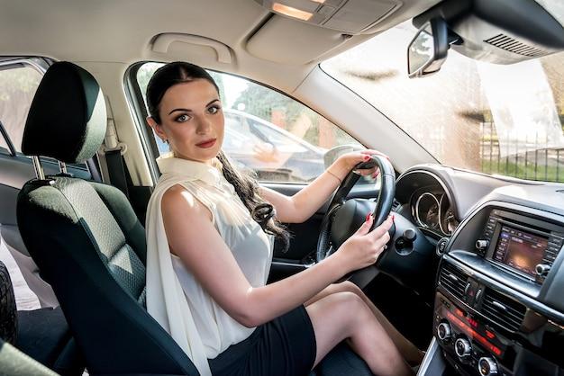 Woman posing inside car sitting in driver seat