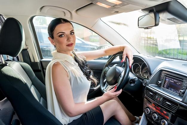 Женщина позирует внутри автомобиля, сидя на сиденье водителя