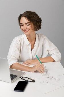 Женщина позирует изолированно над серой стеной, сидя за столом, используя рисунок ноутбука