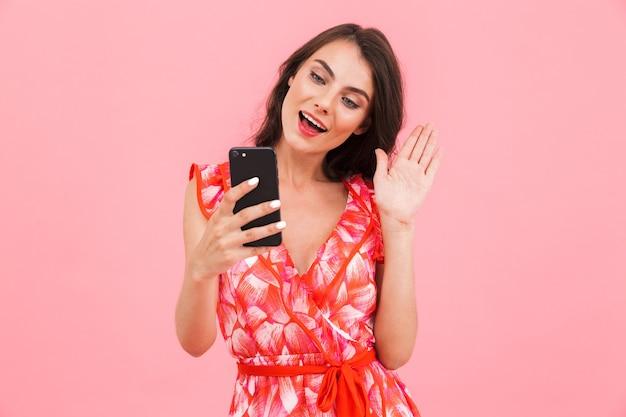 携帯電話で話している孤立した壁をポーズする女性。