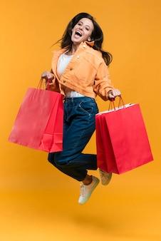 Donna in posa e saltando mentre si tengono le borse della spesa