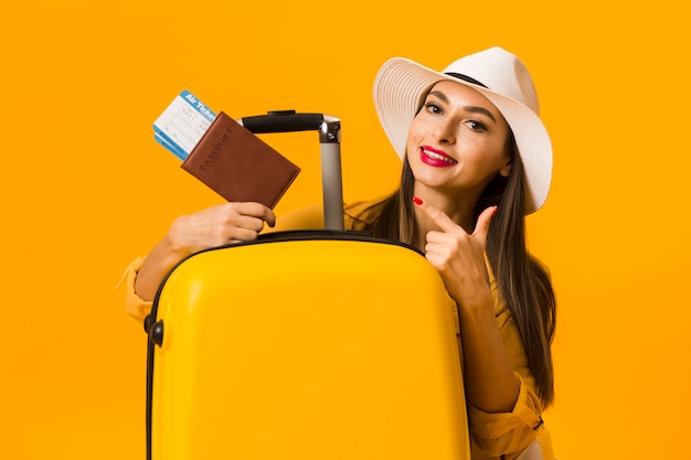 Woman posing next to luggage and pointing at travel essentials