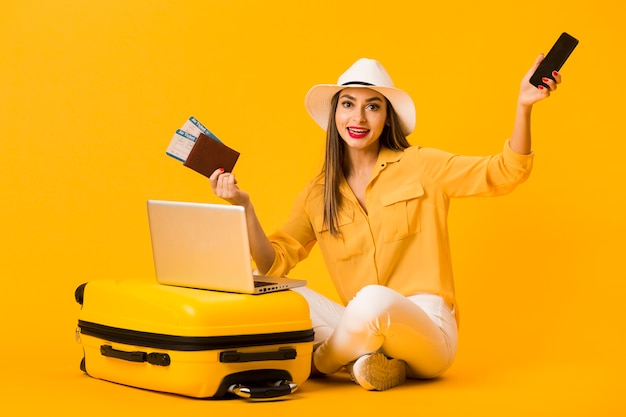 Woman posing next to luggage while holding smartphone and plane tickets