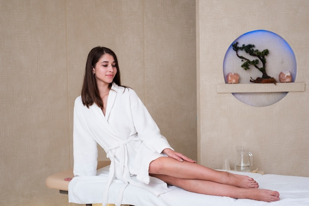 Woman posing on massage table at spa