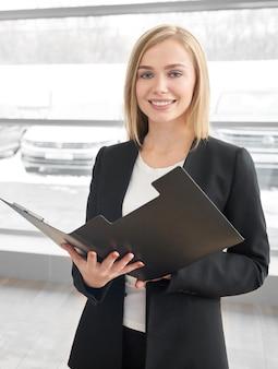 Woman posing near automobile in car dealership.
