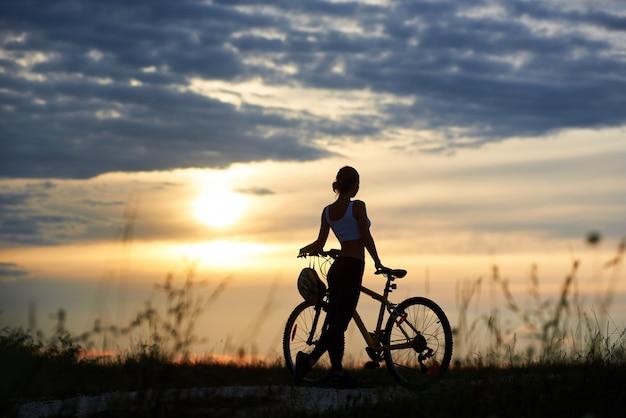 女性が自転車の近くでポーズと自然を不快にさせます。