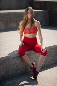 Woman posing near the city fountain in gym clothes after a workout