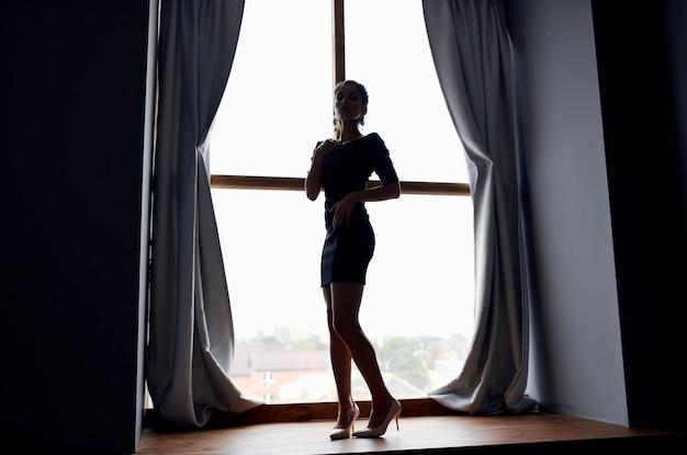 黒のドレスとモデルで大きな窓の近くでポーズをとる女性