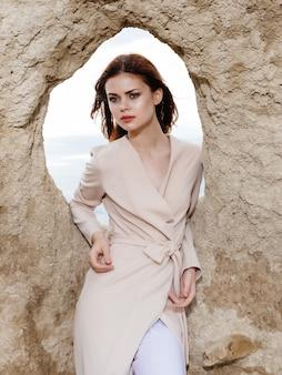 砂のエレガントなスタイルで岩の近くでポーズをとる女性