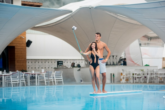 Woman posing near swimming pool making selfie photo with monopod and man standing behind her