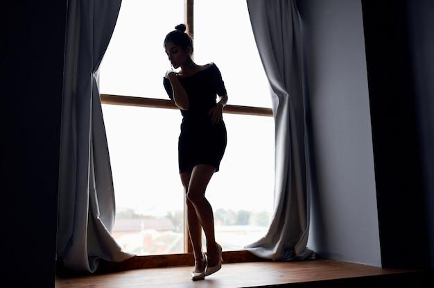 窓の近くでポーズをとる女性エレガントなスタイルの魅力