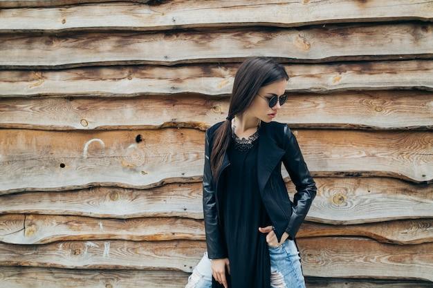 Женщина, стоящая возле деревянной стены