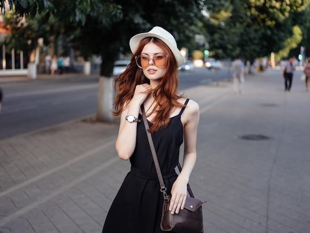 Женщина позирует на сумке шляпа модели природы