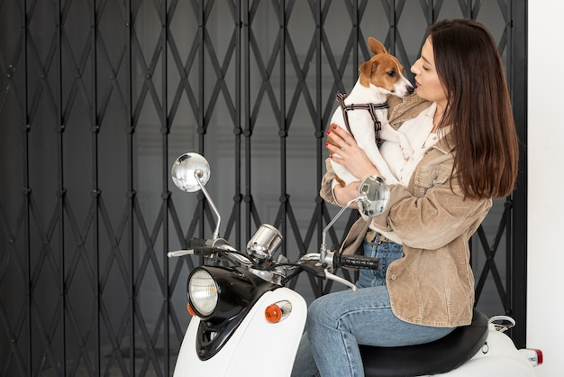 Женщина позирует на скутере, держа ее собаку