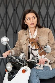 Женщина позирует на скутере со своей собакой
