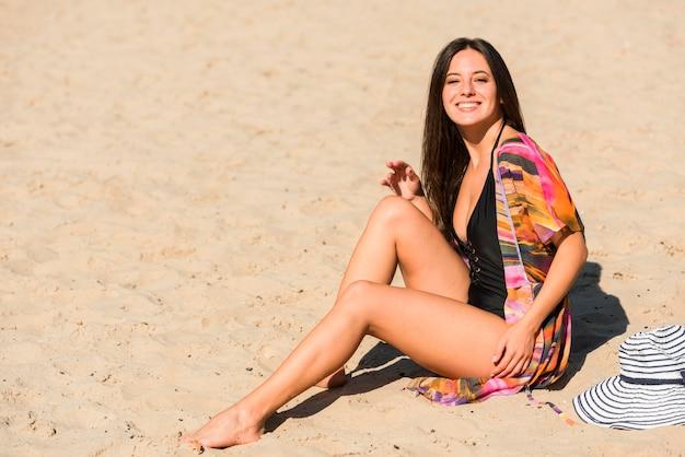 コピースペースでビーチでポーズをとる女性