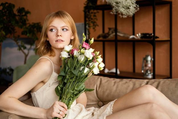 美しい春の花の花束を保持しながらソファでポーズをとる女性