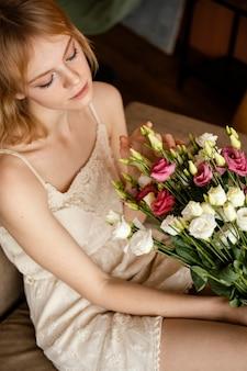 春の花の花束を持ってソファでポーズをとる女性