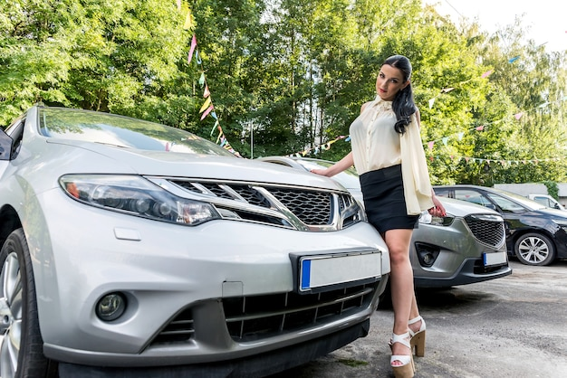 Woman posing outdoors near new car on parking place