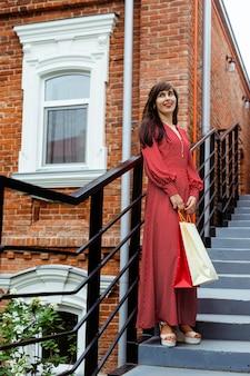 Женщина позирует на улице на ступеньках с хозяйственными сумками