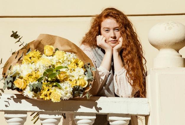 봄 꽃의 부케와 함께 야외에서 포즈를 취하는 여자
