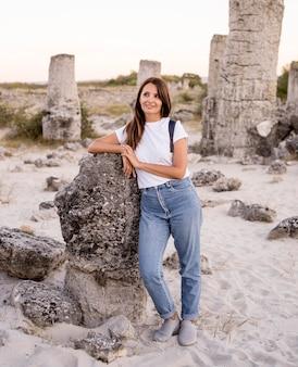 Woman posing next to a rock
