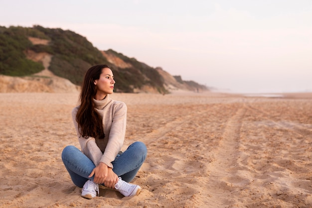 Woman posing on the sand at the beach with copy space