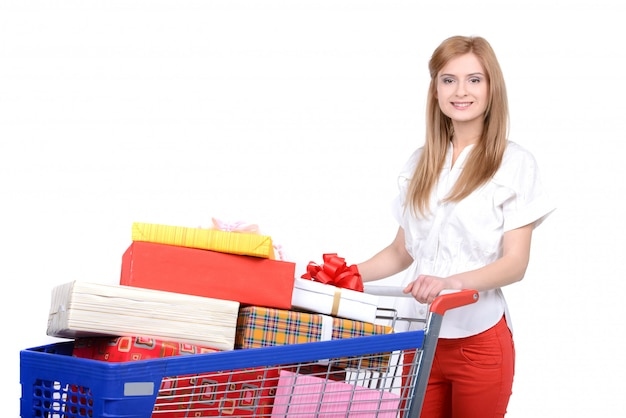A woman posing next to a shopping cart full with gifts.