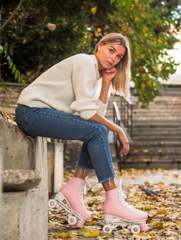 Женщина позирует боком в джинсах и роликовых коньках