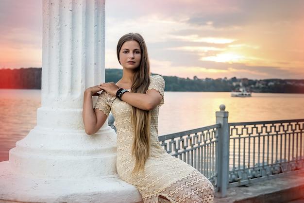 湖岸の列に座ってポーズをとる女性。都市景観