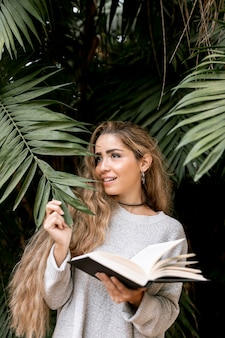 Woman posing behind some leaves while holding a book outside