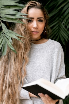 Woman posing behind some leaves while holding a book
