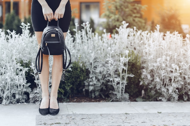 Woman posing in street, holding dark bag