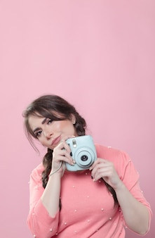 Woman posing while holding camera with copy space