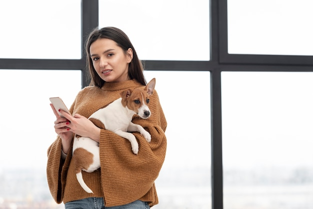 Woman posing while holding dog and smartphone