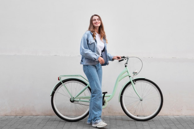 Woman posing while holding her bike outdoors in the city