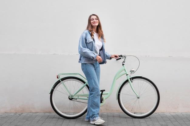 Женщина позирует, держа свой велосипед на открытом воздухе в городе