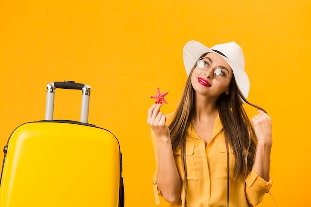 Woman posing while holding a starfish next to luggage
