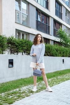 옷 카탈로그의 새로운 컬렉션에서 핸드백과 함께 포즈를 취하는 여자. 세로 사진