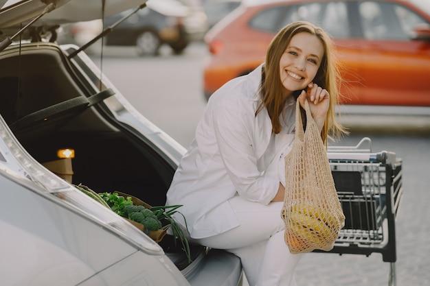 女性が彼女の車で買い物袋でポーズ