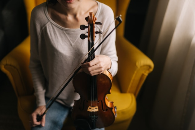 Женщина позирует со скрипкой в руке, сидя на стуле в комнате с современным интерьером
