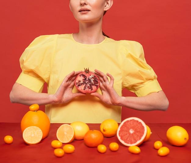 Женщина позирует с композицией из цитрусовых
