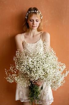 아름 다운 꽃의 부케와 함께 포즈를 취하는 여자