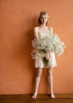 繊細な花の花束でポーズをとる女性