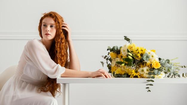 봄 꽃의 부케와 함께 포즈를 취하는 여자