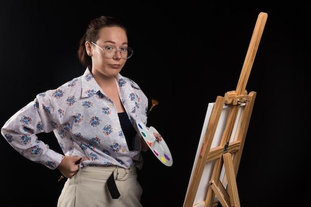 브러시와 캔버스 블랙에 포즈를 취하는 여자. 고품질 사진